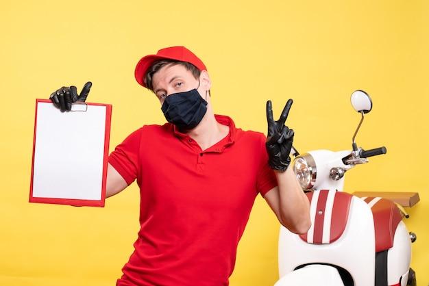 Corriere maschio vista frontale in maschera nera con nota file su lavoro uniforme gialla consegna covid virus lavoro pandemico