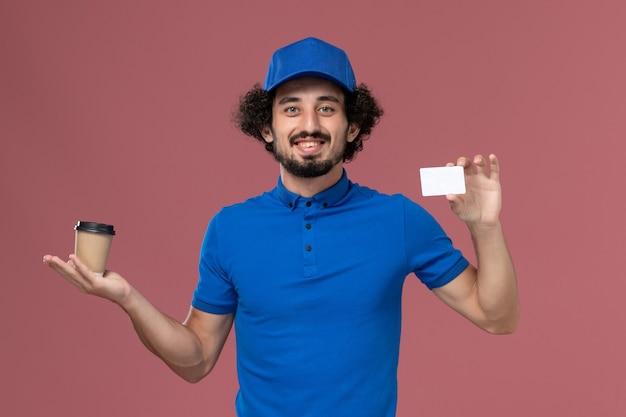Vista frontale del corriere maschio in uniforme blu e cappuccio con tazza di caffè di consegna e carta sulle mani sul muro rosa