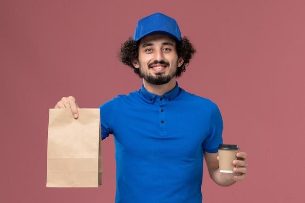 Vista frontale del corriere maschio in uniforme blu e cappuccio con tazza di caffè di consegna e pacchetto di cibo sulle mani sulla parete rosa