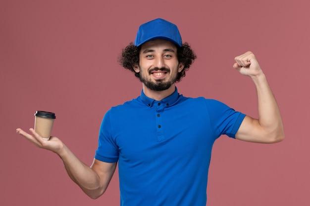 Vista frontale del corriere maschio in uniforme blu e cappuccio con la tazza di caffè di consegna sulle sue mani sul muro rosa
