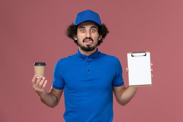 Vista frontale del corriere maschio in uniforme blu e cappuccio con tazza di caffè di consegna e blocco note sulle mani sul muro rosa