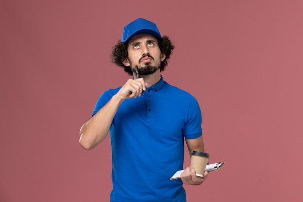 Front view of male courier in blue uniform and cap with delivery coffee cup and notepad on his hands writing notes on pink wall