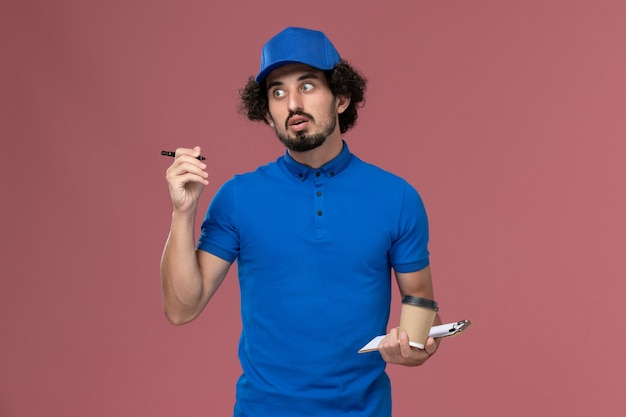 Front view of male courier in blue uniform and cap with delivery coffee cup and notepad on his hands writing notes on the pink wall