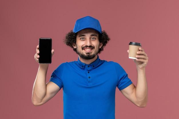 Vista frontale del corriere maschio in uniforme blu e cappuccio con la tazza di caffè di consegna e il telefono sulle mani sul muro rosa