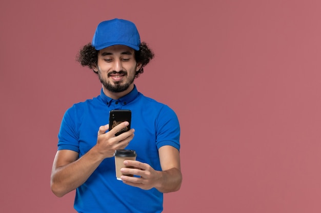 Front view of male courier in blue uniform and cap with delivery coffee cup and smartphone on his hands on pink wall