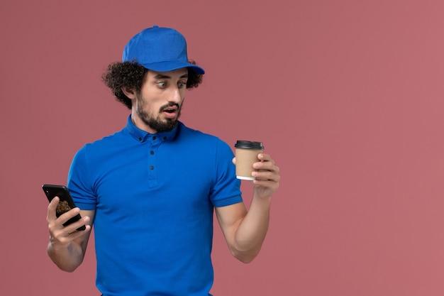 Vista frontale del corriere maschio in uniforme blu e cappuccio con la tazza di caffè di consegna e smartphone sulle sue mani sulla parete rosa