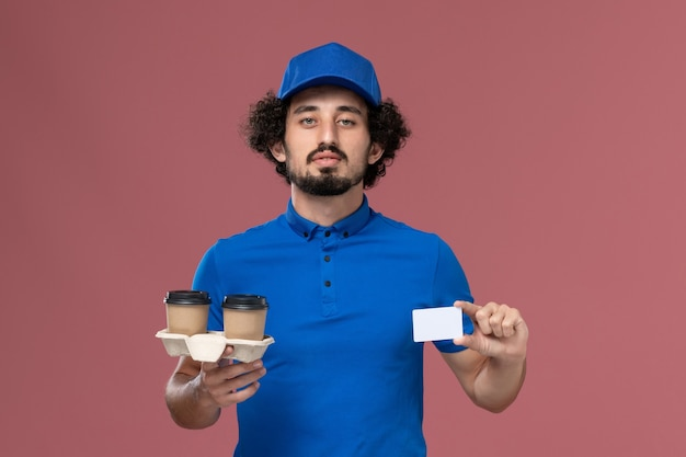 Front view of male courier in blue uniform and cap with delivery coffee cups and card on his hands on the pink wall