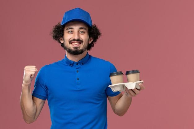 Vista frontale del corriere maschio in protezione uniforme blu con tazze di caffè di consegna sulle sue mani sul muro rosa chiaro
