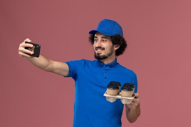 Vista frontale del corriere maschio in protezione uniforme blu con tazze di caffè di consegna sulle sue mani, scattare una foto sulla parete rosa