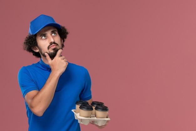 Vista frontale del corriere maschio in protezione uniforme blu con tazze di caffè di consegna sulle sue mani e pensando sulla scrivania rosa