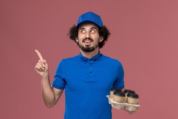 Vista frontale del corriere maschio in protezione uniforme blu con tazze di caffè di consegna sulle mani e pensare sulla parete rosa