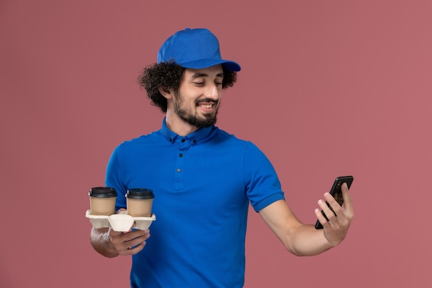 Front view of male courier in blue uniform and cap with delivery coffee cups and work phone on his hands on the pink wall