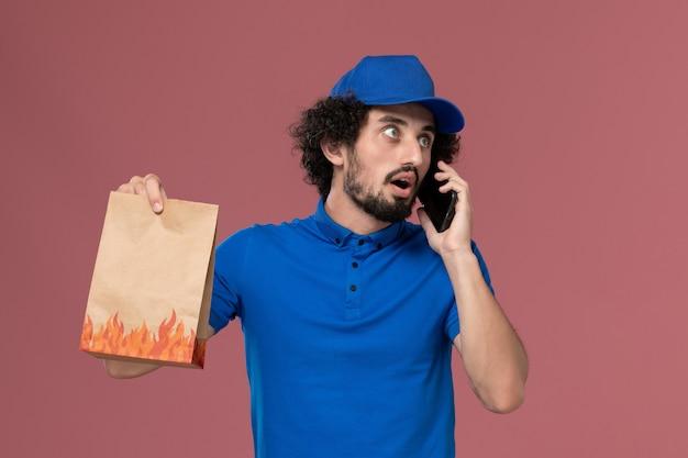 Vista frontale del corriere maschio in protezione uniforme blu con il pacchetto di cibo di consegna sulle sue mani parlando al telefono sulla parete rosa