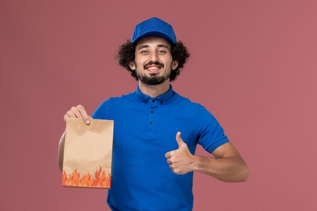 Front view of male courier in blue uniform cap with delivery paper food package on his hands on the light pink wall