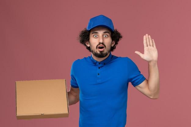Vista frontale del corriere maschio in berretto blu uniforme con scatola di cibo sulle mani sulla parete rosa chiaro