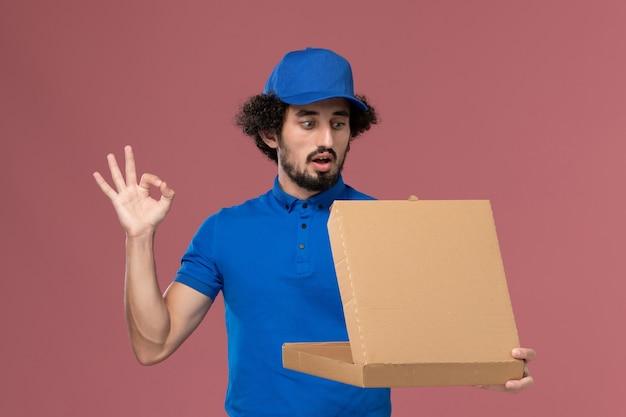 Vista frontale del corriere maschio in berretto blu uniforme con scatola di cibo sulle sue mani aprendolo sul muro rosa chiaro