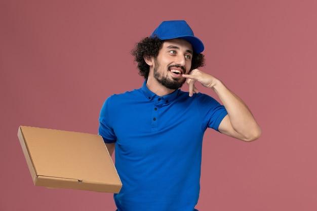 Vista frontale del corriere maschio in protezione uniforme blu con scatola di cibo sulle mani in posa sul muro rosa chiaro