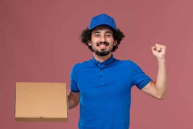 Vista frontale del corriere maschio in berretto blu uniforme con scatola di cibo sulle sue mani che si rallegrano sulla parete rosa chiaro