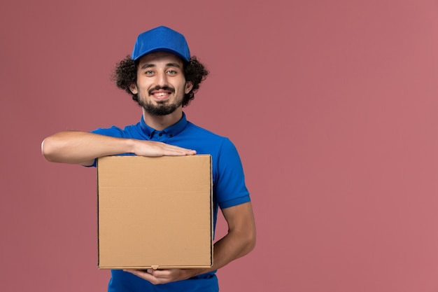 Front view of male courier in blue uniform cap with food box on his hands smiling on light-pink wall
