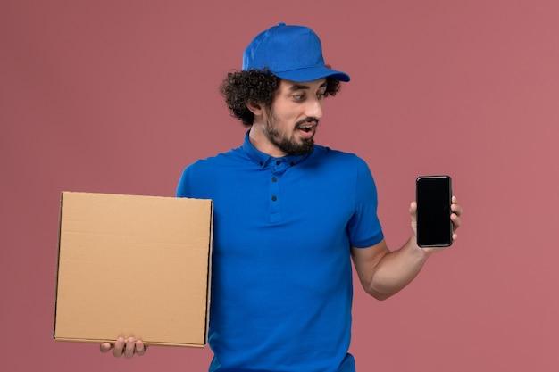 Vista frontale del corriere maschio in berretto blu uniforme con scatola di cibo e telefono sulle mani sul muro rosa chiaro