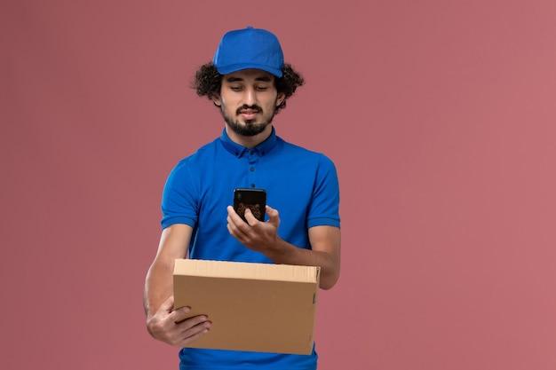 Vista frontale del corriere maschio in protezione uniforme blu con scatola di cibo e telefono sulle mani sulla parete rosa