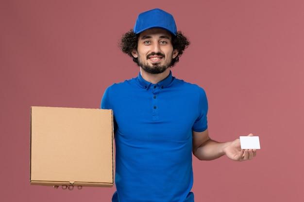 Vista frontale del corriere maschio in protezione uniforme blu con scatola di cibo e carta di plastica bianca sulle sue mani sul muro rosa