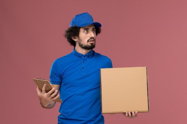 Vista frontale del corriere maschio in protezione uniforme blu con blocco note e scatola di cibo sulle sue mani sulla parete rosa