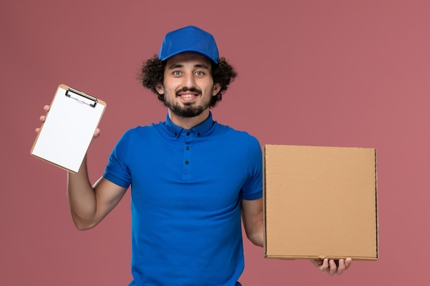 Front view of male courier in blue uniform cap with notepad and food box on his hands on pink wall