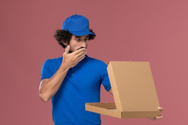 Vista frontale del corriere maschio in berretto blu uniforme con scatola di cibo aperta sulle mani sulla parete rosa chiaro