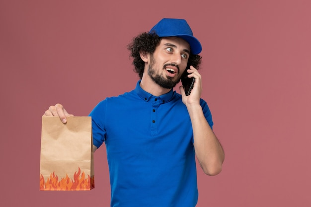 Front view of male courier in blue uniform cap with smartphone and delivery food package on his hands on the pink wall