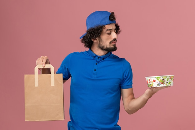 Corriere maschio di vista frontale in uniforme blu e mantello che tiene il pacchetto di cibo di consegna e ciotola sull'uniforme di servizio di consegna della parete rosa