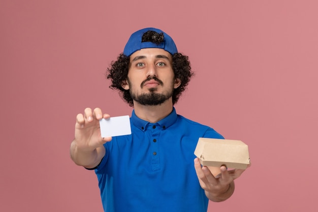 Front view male courier in blue uniform and cape holding delivery food package and card on pink wall uniform delivery service job