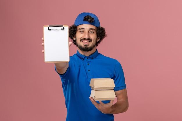 Corriere maschio di vista frontale in uniforme blu e mantello che tiene i pacchetti di cibo di consegna con il blocco note sul lavoro maschio di servizio di consegna uniforme della parete rosa