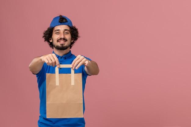 Corriere maschio di vista frontale in uniforme blu e mantello che tiene il pacchetto di cibo di carta di consegna sulla uniforme di lavoro di servizio di consegna della parete rosa