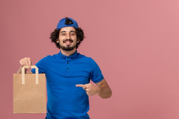 Front view male courier in blue uniform and cape holding delivery paper food package smiling on pink wall delivery service uniform