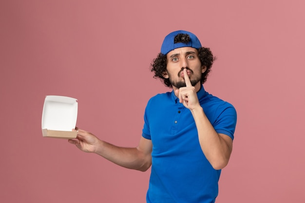 Front view male courier in blue uniform and cape holding empty little delivery food package on the pink wall uniform delivery service company