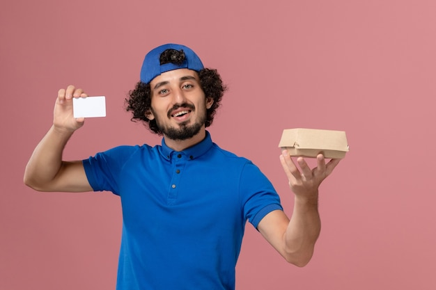 Front view male courier in blue uniform and cape holding little delivery food package and card on pink wall uniform delivery worker service