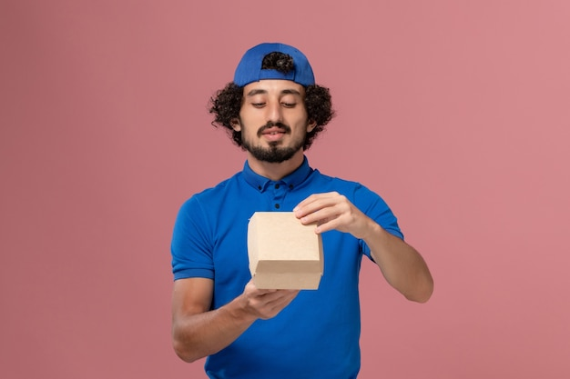 Front view male courier in blue uniform and cape holding little delivery food package and opening it on the pink wall uniform delivery service company