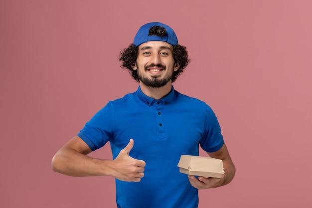 Corriere maschio di vista frontale in uniforme blu e mantello che tiene piccolo pacchetto di cibo di consegna sull'impiegato di lavoro dell'azienda di servizio di consegna uniforme della parete rosa