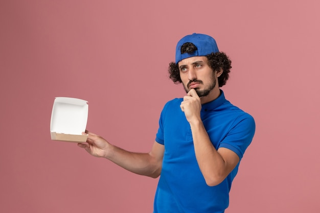 Corriere maschio di vista frontale in uniforme blu e mantello che tiene piccolo pacchetto di cibo di consegna e pensa alla società di servizi di consegna uniforme della parete rosa