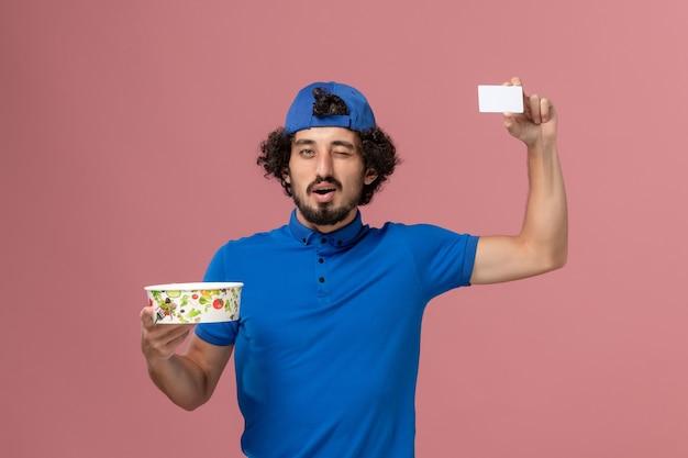 Corriere maschio di vista frontale in uniforme blu e mantello che tiene la ciotola e la carta rotonde di consegna sulla parete rosa