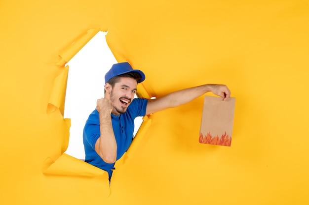 Corriere maschio vista frontale in uniforme blu che dà pacchetto di cibo su spazio giallo yellow