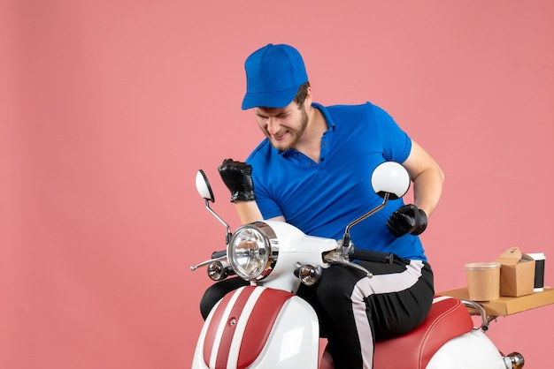 Front view male courier in blue uniform and gloves rejoicing on pink color work fast-food bike service food job delivery