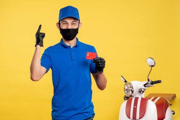 Corriere maschio di vista frontale in uniforme blu che tiene la carta di credito sul servizio di lavoro giallo covid - uniforme di colore pandemico di consegna del lavoro