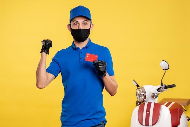 Corriere maschio di vista frontale in uniforme blu che tiene la carta di credito sul colore giallo di consegna del covid-lavoro dell'uniforme di servizio di lavoro
