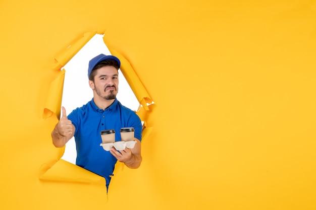 Corriere maschio vista frontale in uniforme blu che tiene tazze di caffè su spazio giallo yellow