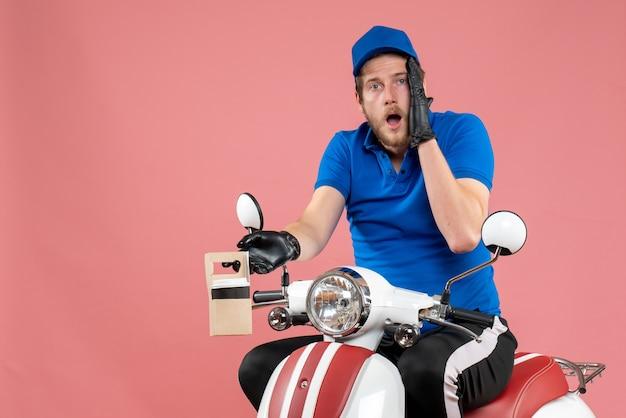 Corriere maschio di vista frontale in uniforme blu che tiene caffè sul lavoratore di servizio di bici di consegna del lavoro di fast-food di colore rosa del lavoro