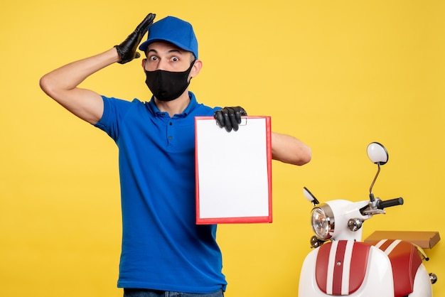 Front view male courier in blue uniform holding file note on a yellow job service covid- delivery pandemic color uniform work