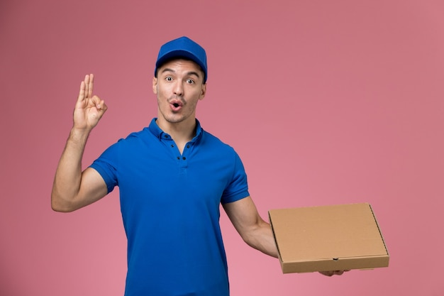 Front view male courier in blue uniform holding food box posing on the pink wall, job worker uniform service delivery