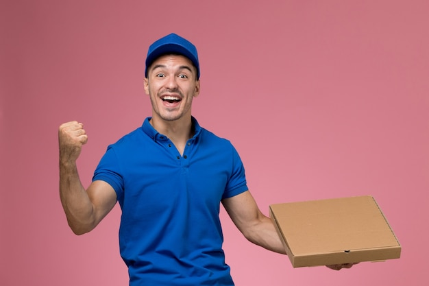Front view male courier in blue uniform holding food box rejoicing on the pink wall, job worker uniform service delivery